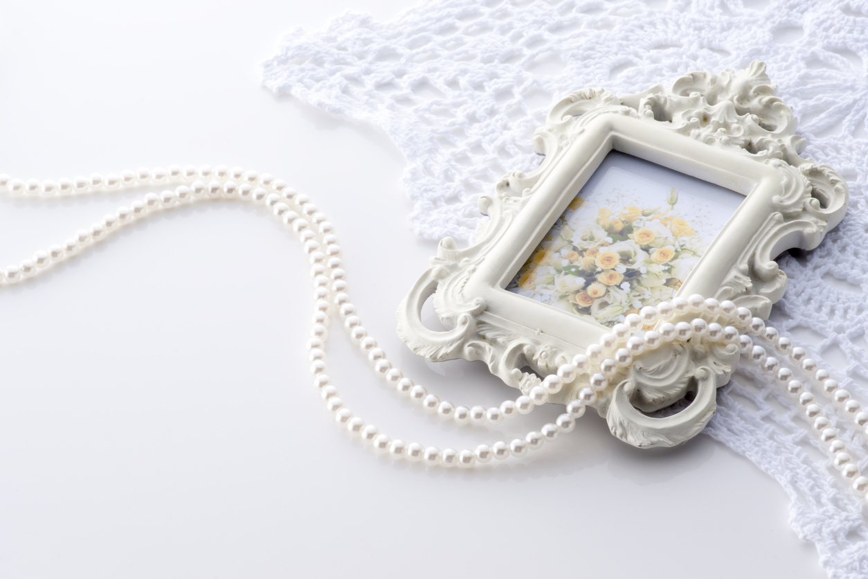 Picture frame and pearl jewellery on white lace